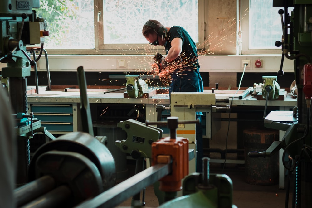 a person using a machine saw to cut metal