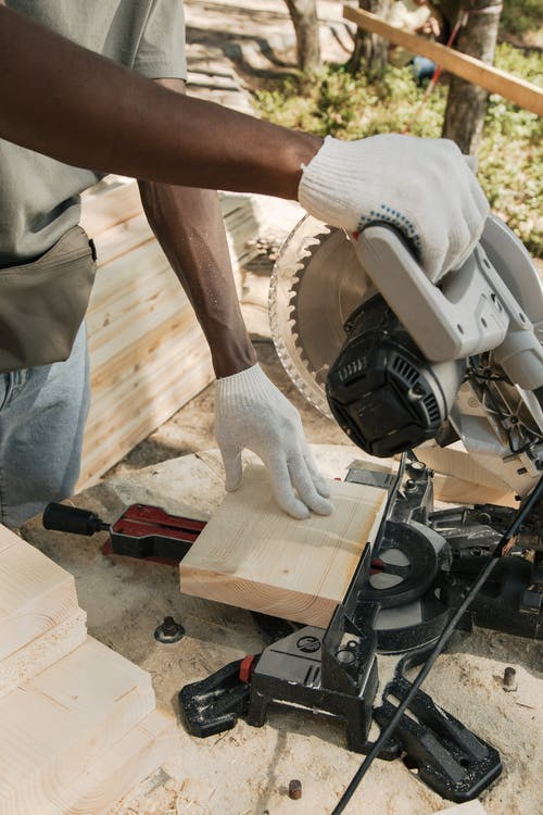 a person using a machine saw to cut wood